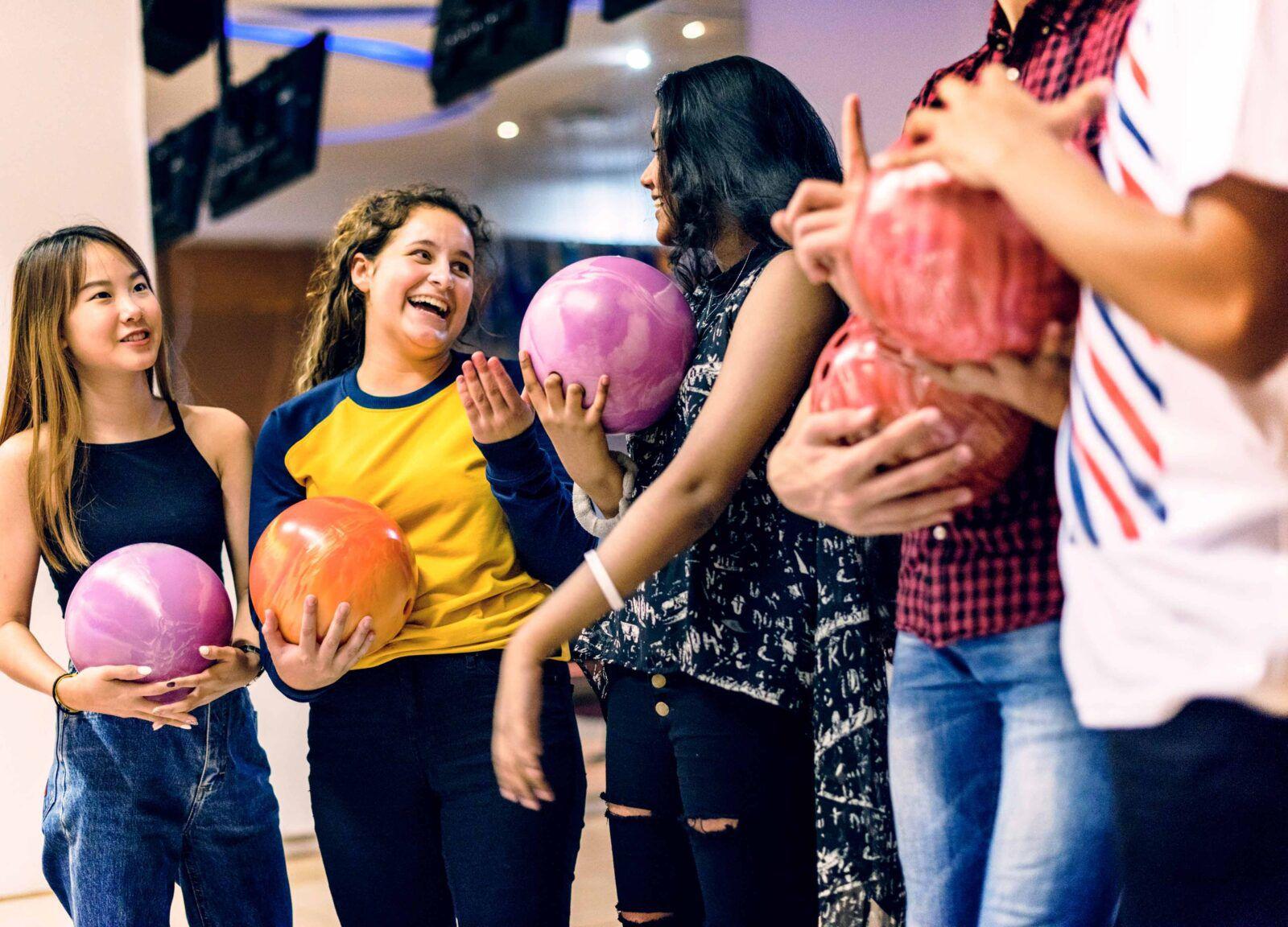 Grupp ungdomar spelar bowling
